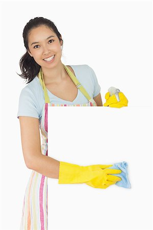 rubber apron woman - Cheerful woman wiping down white surface in apron and rubber gloves Stock Photo - Budget Royalty-Free & Subscription, Code: 400-06866436