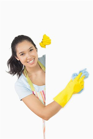 rubber apron woman - Smiling woman in apron and rubber gloves cleaning white surface Stock Photo - Budget Royalty-Free & Subscription, Code: 400-06866438