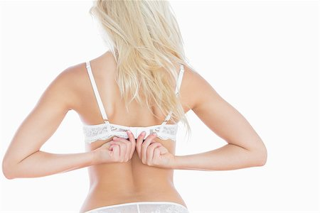 Rear view of young woman fastening bra strap over white background Stock Photo - Budget Royalty-Free & Subscription, Code: 400-06869831