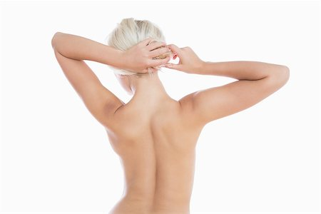 Rear view of topless woman tying hair over white background Stock Photo - Budget Royalty-Free & Subscription, Code: 400-06869855