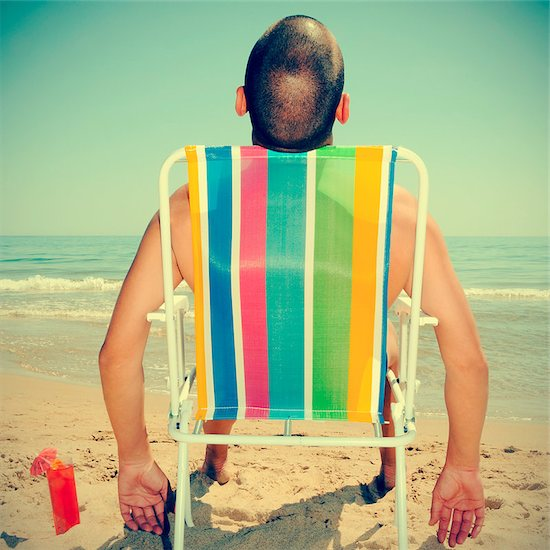 picture of a man sunbathing on a deckchair on the beach with a cocktail, with a retro effect Stock Photo - Royalty-Free, Artist: nito, Image code: 400-06861816