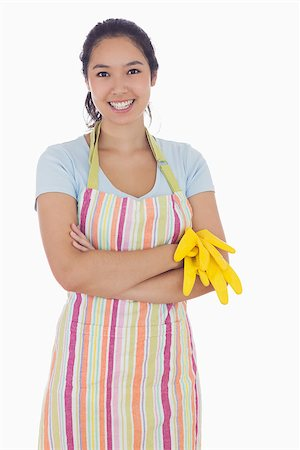 rubber apron woman - Woman smiling while holding rubber gloves and wearing an apron Stock Photo - Budget Royalty-Free & Subscription, Code: 400-06863559