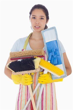 rubber apron woman - Frowning woman in apron and rubber gloves holding brushes and mops Stock Photo - Budget Royalty-Free & Subscription, Code: 400-06863565