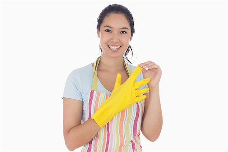 rubber apron woman - Smiling woman standing and taking off rubber gloves while wearing an apron Stock Photo - Budget Royalty-Free & Subscription, Code: 400-06863560