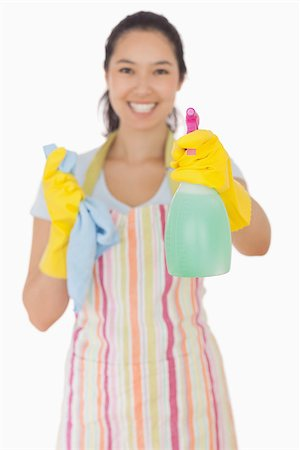 rubber apron woman - Happy woman in apron and rubber gloves holding out spray bottle Stock Photo - Budget Royalty-Free & Subscription, Code: 400-06863593