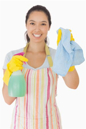 rubber apron woman - Smiling young woman holding up rag and spray bottle in apron and rubber gloves Stock Photo - Budget Royalty-Free & Subscription, Code: 400-06863642
