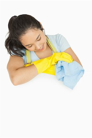 rubber apron woman - Happy woman with blue rag leaning on white surface wearing rubber gloves and apron Stock Photo - Budget Royalty-Free & Subscription, Code: 400-06863657