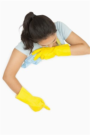 rubber apron woman - Smiling woman in rubber gloves and apron pointing on white surface Stock Photo - Budget Royalty-Free & Subscription, Code: 400-06863658
