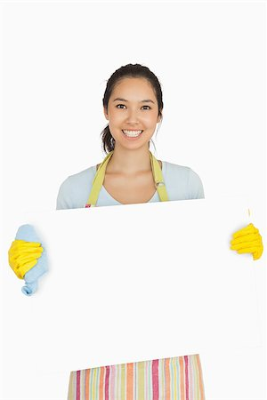 rubber apron woman - Smiling woman in apron and rubber gloves holding white surface Stock Photo - Budget Royalty-Free & Subscription, Code: 400-06863669