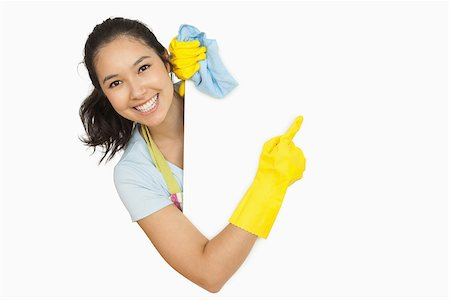 rubber apron woman - Woman in rubber gloves and apron pointing to the white surface she is behind Stock Photo - Budget Royalty-Free & Subscription, Code: 400-06863660