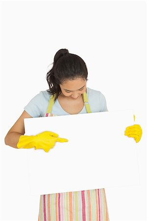 rubber apron woman - Happy woman in rubber gloves and apron pointing to white surface she is holding Stock Photo - Budget Royalty-Free & Subscription, Code: 400-06863675