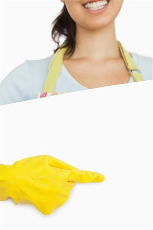 rubber apron woman - Smiling woman in rubber gloves and apron standing behind board and pointing Stock Photo - Budget Royalty-Free & Subscription, Code: 400-06863679