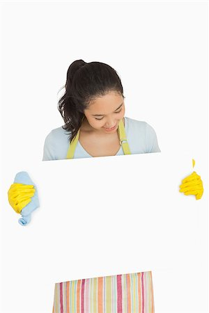 rubber apron woman - Happy woman in rubber gloves and apron looking at white surface she is holding Stock Photo - Budget Royalty-Free & Subscription, Code: 400-06863670