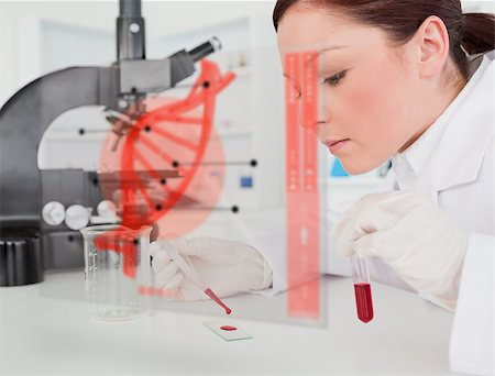 Scientist pouring drop of blood onto glass with futuristic interface in front of her showing DNA Stock Photo - Budget Royalty-Free & Subscription, Code: 400-06877723