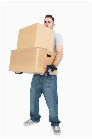Portrait of young man carrying package boxes over white background Stock Photo - Budget Royalty-Free & Subscription, Code: 400-06870407