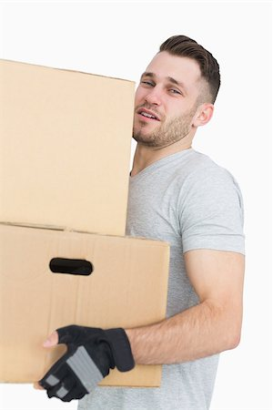 Portrait of tired young man carrying package boxes over white background Stock Photo - Budget Royalty-Free & Subscription, Code: 400-06870410