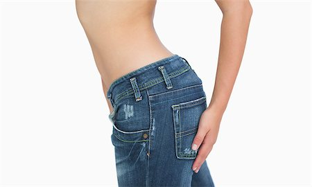 Side midsection of slim woman in jeans standing over white background Stock Photo - Budget Royalty-Free & Subscription, Code: 400-06870800