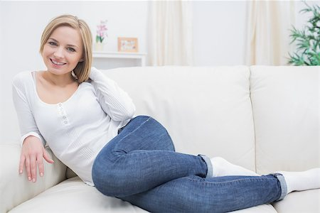 Portrait of casual happy young woman sitting on sofa at home Stock Photo - Budget Royalty-Free & Subscription, Code: 400-06872348