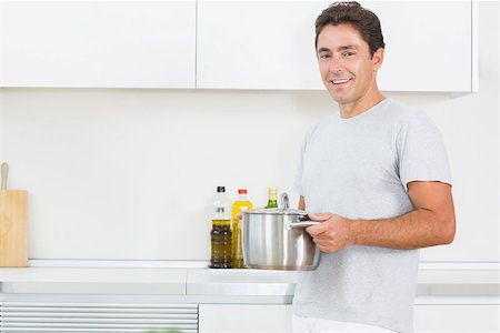 Handsome man carrying large pot through kitchen Stock Photo - Budget Royalty-Free & Subscription, Code: 400-06872682