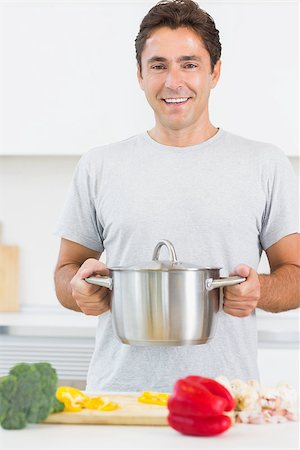 Man holding large pot in front of chopping board with vegetables in kitchen Stock Photo - Budget Royalty-Free & Subscription, Code: 400-06872683