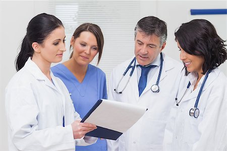 Nurse and doctors looking at clipboard smiling in office Stock Photo - Budget Royalty-Free & Subscription, Code: 400-06873884