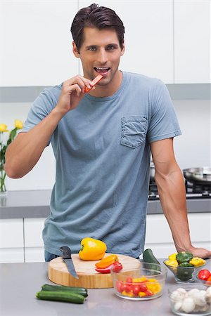 pimento - Attractive man eating a slice of bell pepper in the kitchen Stock Photo - Budget Royalty-Free & Subscription, Code: 400-06888313