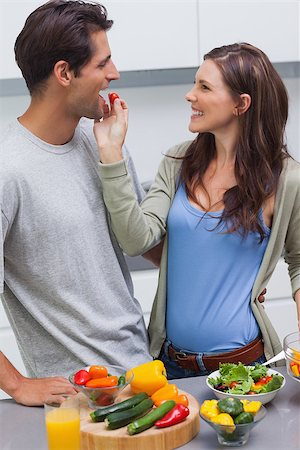 pimento - Attractive woman feeding her husband cherry tomato in kitchen Stock Photo - Budget Royalty-Free & Subscription, Code: 400-06888327