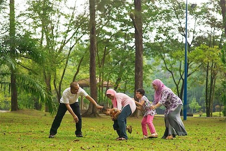 family fun day background - Muslim family having fun at green outdoor park. Beautiful Southeast Asian family playing together. Stock Photo - Budget Royalty-Free & Subscription, Code: 400-06915049