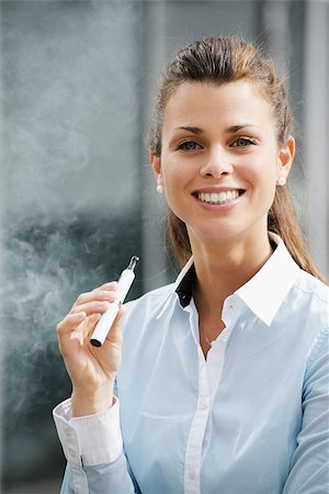 diego_cervo (artist) - portrait of young female smoker smoking e-cigarette outdoor office building and looking at camera Stock Photo - Budget Royalty-Free & Subscription, Code: 400-06926267