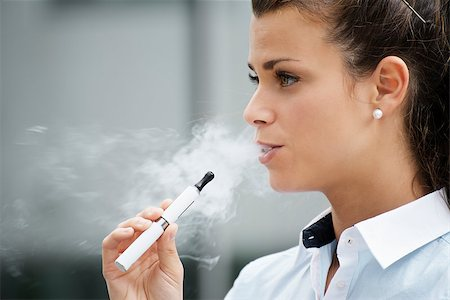 diego_cervo (artist) - young female smoker smoking e-cigarette outdoors. Head and shoulders, side view Stock Photo - Budget Royalty-Free & Subscription, Code: 400-06928035