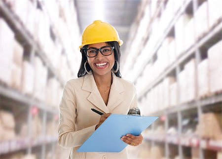 Smiling Indian woman doing stock tick in warehouse  with safety helmet smiling happy writing report. Portrait of beautiful Asian female model standing inside factory. Stock Photo - Budget Royalty-Free & Subscription, Code: 400-06922030