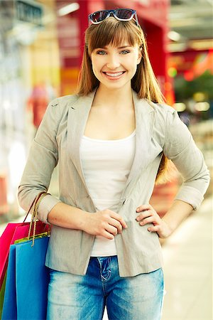 Vertical portrait of a happy young woman being occupied with her favorite activity - shopping Stock Photo - Budget Royalty-Free & Subscription, Code: 400-06923013