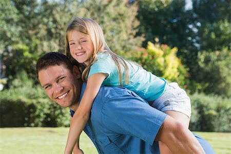Daughter getting piggy back from dad in a park smiling at camera Stock Photo - Budget Royalty-Free & Subscription, Code: 400-06934004