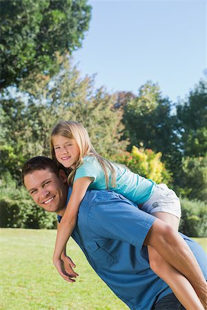 Daughter getting piggy back from dad smiling at camera in the park on a sunny day Stock Photo - Budget Royalty-Free & Subscription, Code: 400-06934005