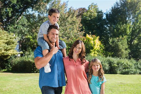 Cute family smiling at camera in the park on a sunny day Stock Photo - Budget Royalty-Free & Subscription, Code: 400-06934007