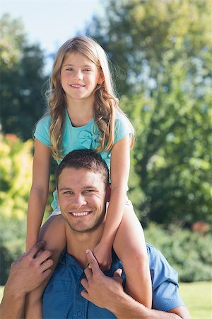 Young girl sitting on her dads shoulder and looking at a camera in the park Stock Photo - Budget Royalty-Free & Subscription, Code: 400-06934002