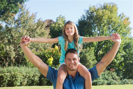 Daughter sitting on dads shoulder and stretching her arms in the park Stock Photo - Budget Royalty-Free & Subscription, Code: 400-06934003