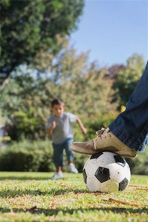 Boy running towards the football under dads foot in the park Stock Photo - Budget Royalty-Free & Subscription, Code: 400-06934014