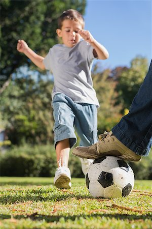 Boy kicking the football from under dads foot in the park Stock Photo - Budget Royalty-Free & Subscription, Code: 400-06934015