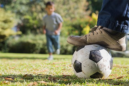 Child running for the football under his fathers foot in the park Stock Photo - Budget Royalty-Free & Subscription, Code: 400-06934011
