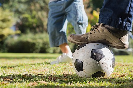 Child kicking the ball from fathers foot in the park Stock Photo - Budget Royalty-Free & Subscription, Code: 400-06934012