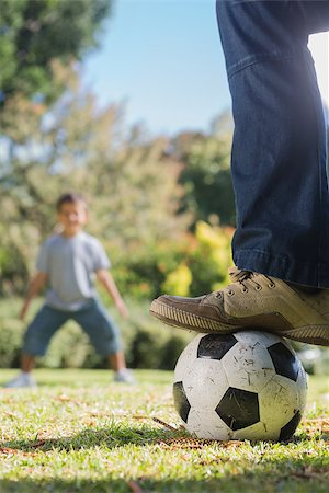 Child waiting for the football under fathers foot in the park Stock Photo - Budget Royalty-Free & Subscription, Code: 400-06934013