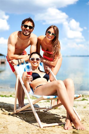 Relaxed young friends having rest on the beach on a sunny day Stock Photo - Budget Royalty-Free & Subscription, Code: 400-06934874