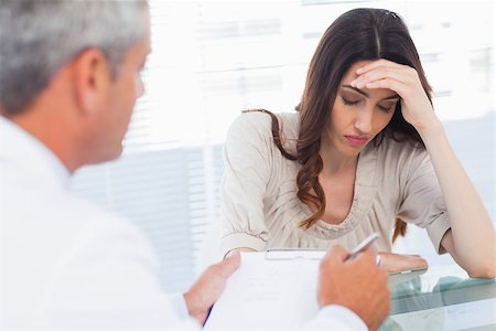 Upset woman listening to her docter talking about a illness in medical office Stock Photo - Budget Royalty-Free & Subscription, Code: 400-06930481