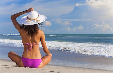 simsearch:400-04002563,k - A sexy young brunette woman or girl wearing a bikini and sun hat sitting on a deserted tropical beach with a blue sky Stock Photo - Budget Royalty-Free & Subscription, Code: 400-06947603