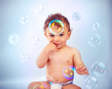 Photo of adorable baby boy isolated on blue background, sweet child sitting and playing with soap bubbles, cute kid bathing with soap-bubbles, portrait of smiling toddler in diaper Stock Photo - Budget Royalty-Free & Subscription, Code: 400-06954051