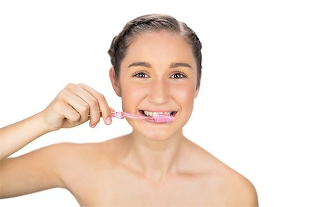 Smiling young model on white background brushing her teeth Stock Photo - Budget Royalty-Free & Subscription, Code: 400-06956498