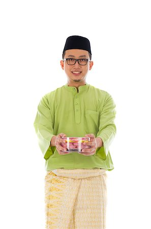 Traditional Malay male with biscuit during hari raya Stock Photo - Budget Royalty-Free & Subscription, Code: 400-07043425