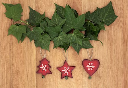 Old wooden christmas decorations hanging from ivy leaf sprigs over oak background. Stock Photo - Budget Royalty-Free & Subscription, Code: 400-07087007