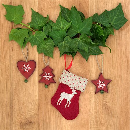 Christmas eve symbols of red stocking, tree, star and heart with ivy leaf sprigs over oak background. Stock Photo - Budget Royalty-Free & Subscription, Code: 400-07087002